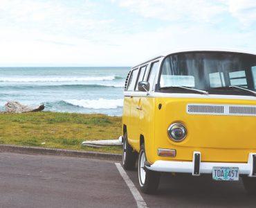 Yellow VW camper van on the ocean shore