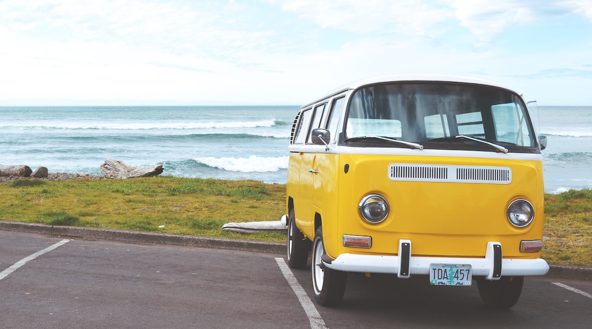 Yellow VW camper van on the ocean shore